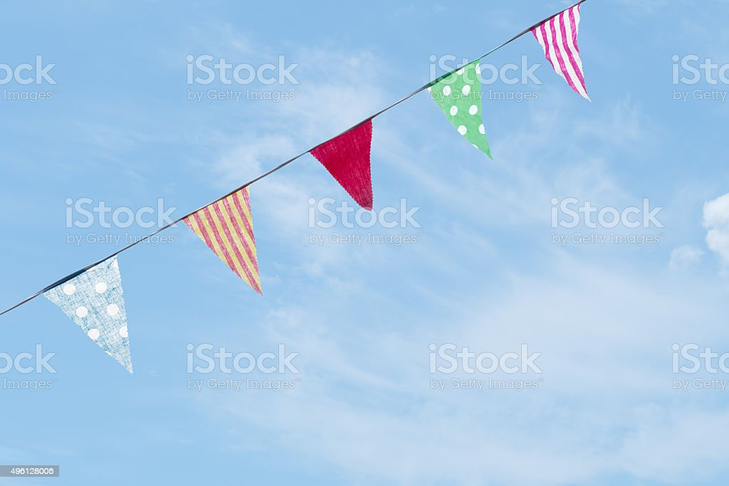 Photo of fabric bunting, flags, over slue sky with clouds. stock photo