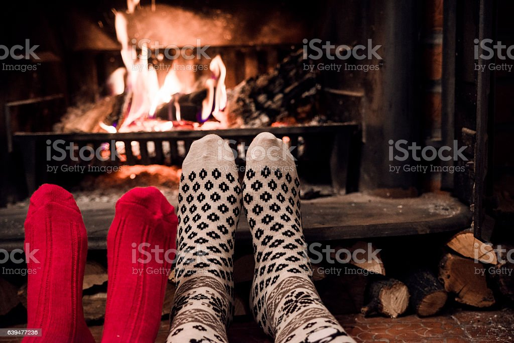 Photo of Feet in woollen socks by the Christmas fireplace stock photo