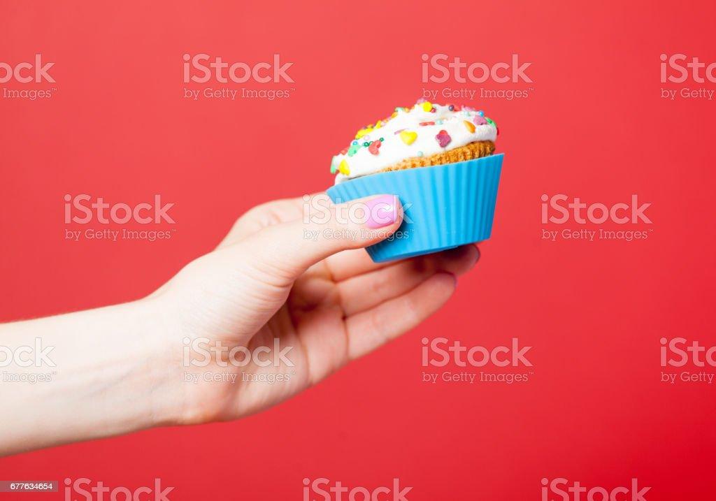 photo of female hand holding cupcake on the wonderful red background stock photo