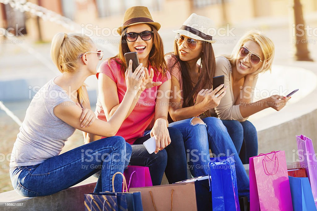 Photo of four young shopping women looking at smartphone stock photo