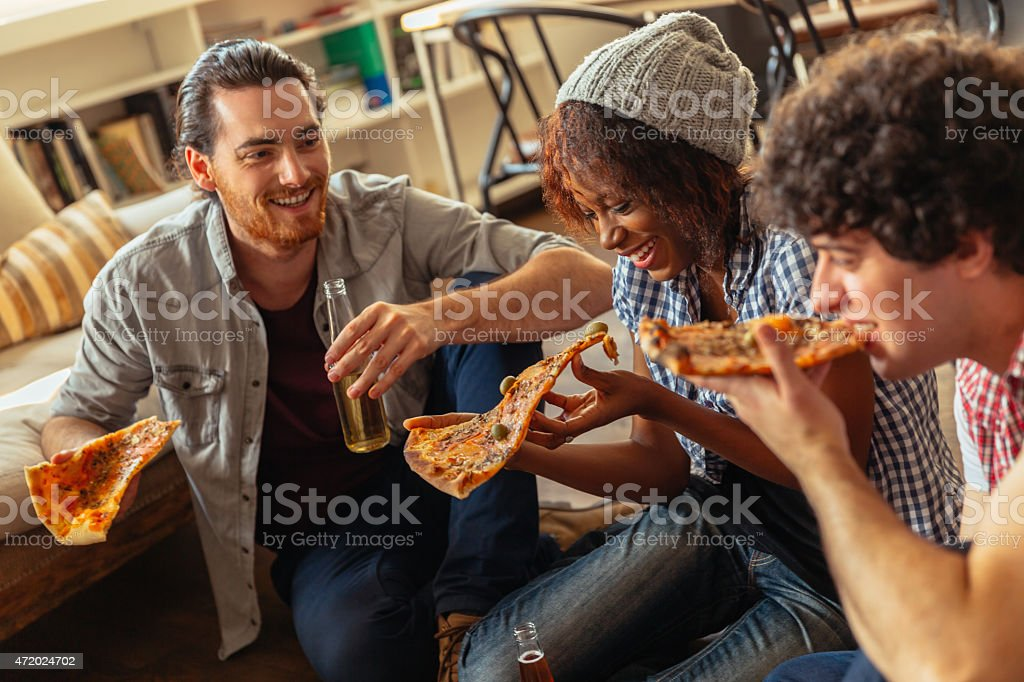 Photo of friends enjoying pizza at home stock photo