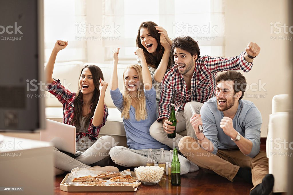Photo of friends watching football game and eating pizza stock photo