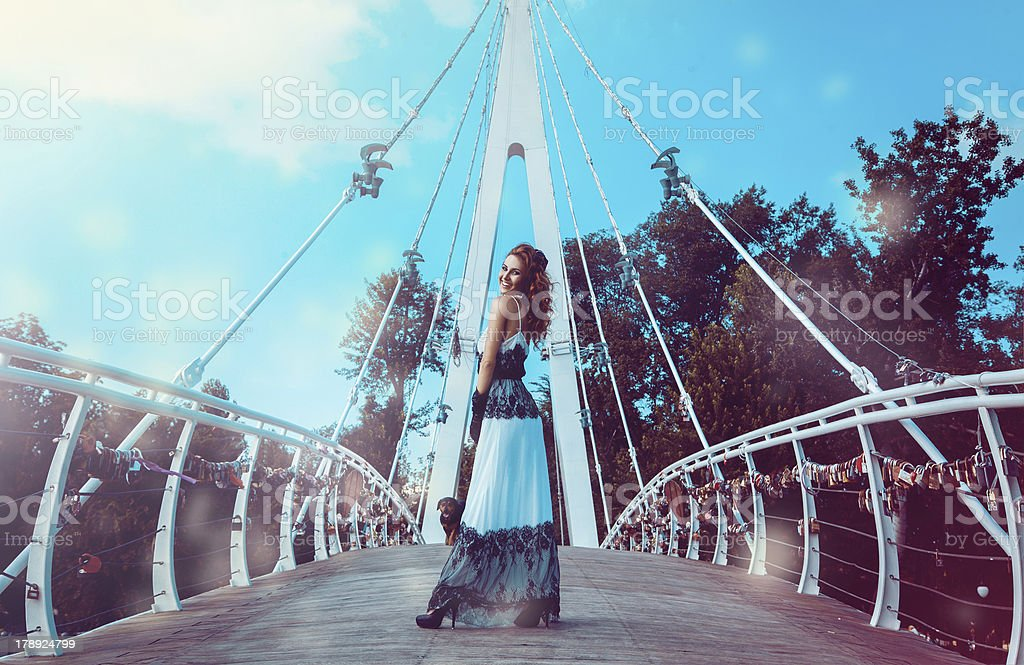 Photo of funny woman on bridge with dog behind royalty-free stock photo