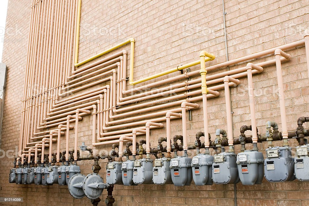 Photo of gas meters connected to gas line on a brick wall stock photo
