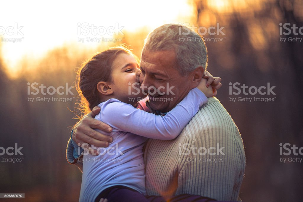 Photo of grandfather and his granddaughter in the park stock photo
