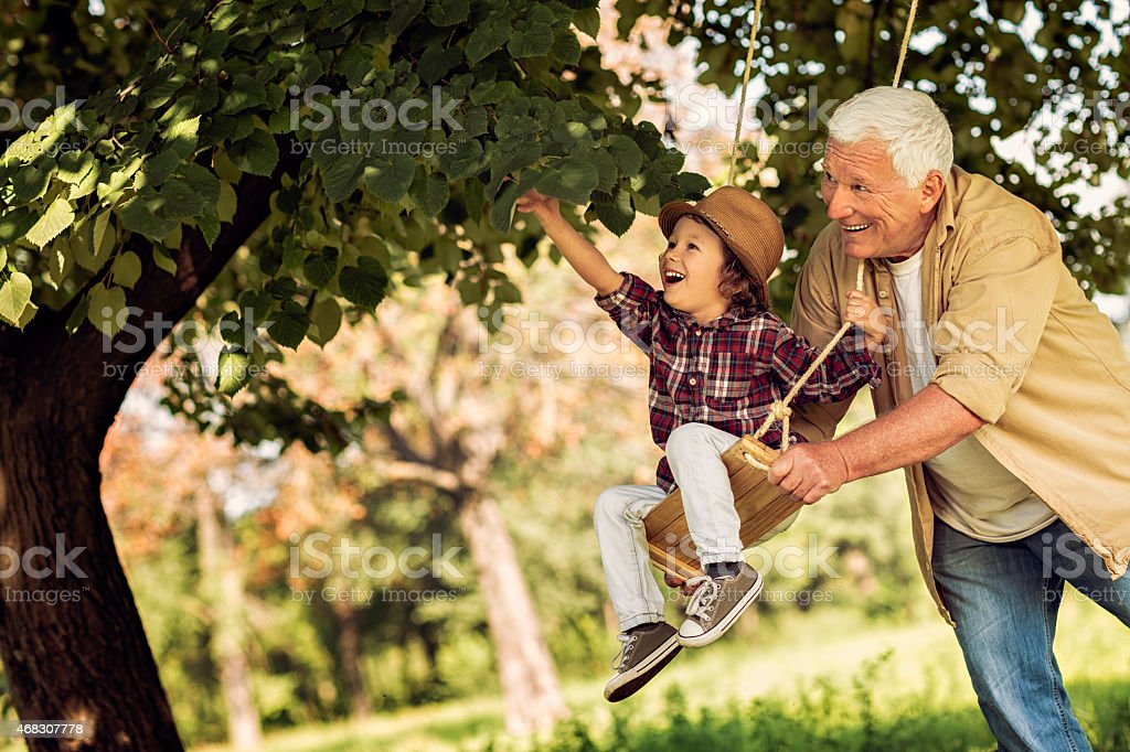 Photo of grandfather pushing grandson on a swing stock photo