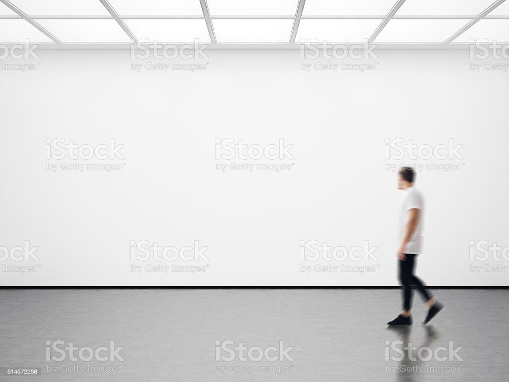 Photo of hipster in modern gallery looking at the empty stock photo