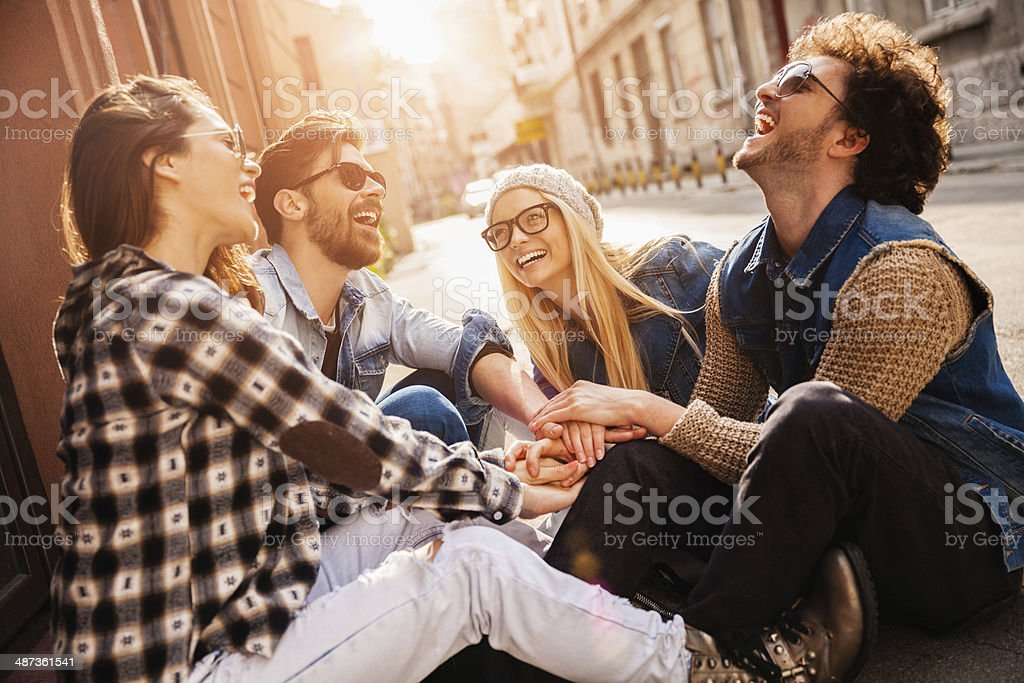 Photo of laughing friends joining hands outdoors stock photo