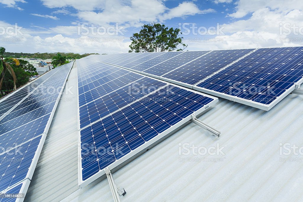 Photo of long grid of solar panels on a metal roof stock photo