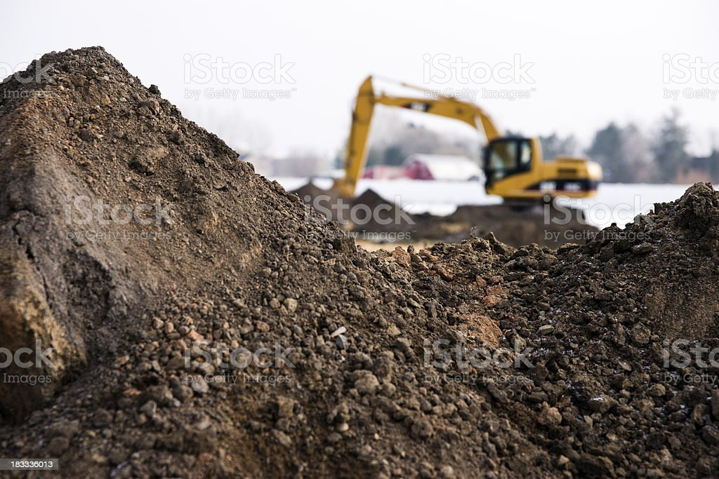Photo of machinery and dirt piles during winter construction stock photo