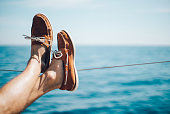 Photo of man legs on the yacht and wearing boat