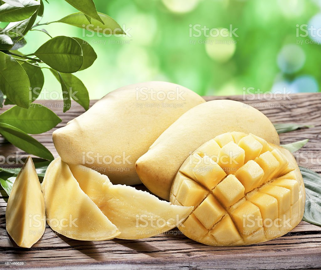 Photo of mango fruits on a wooden table. stock photo