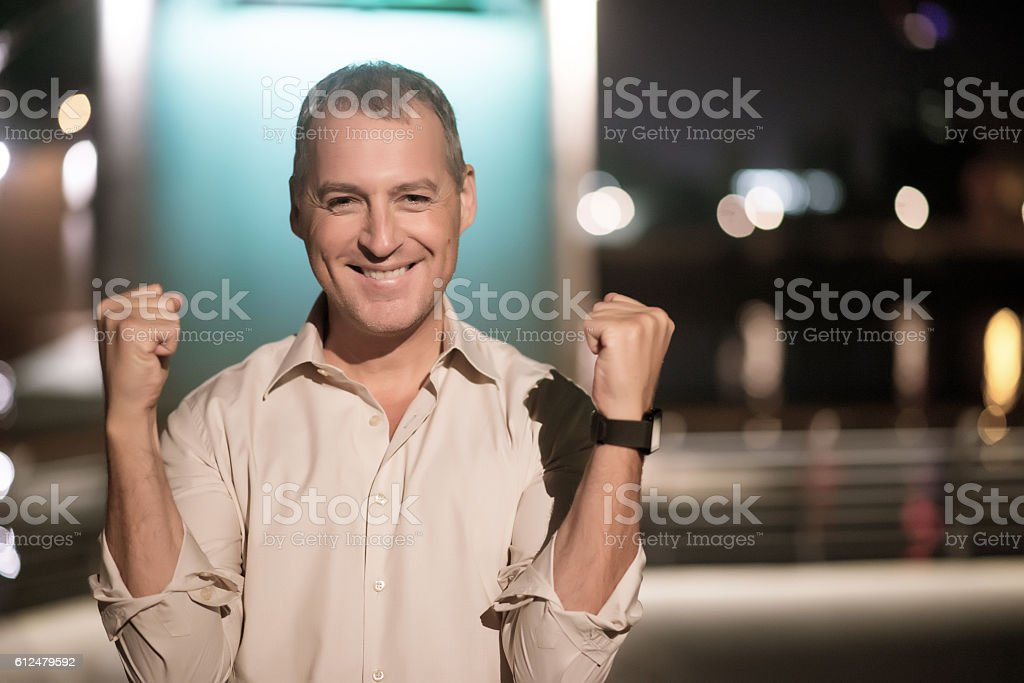 Photo of mature man with arms up standing by night stock photo