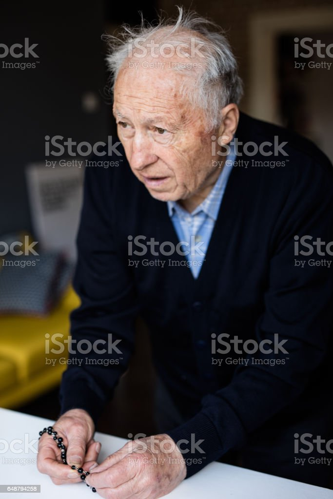 Photo of sad old man praying to God with rosary stock photo
