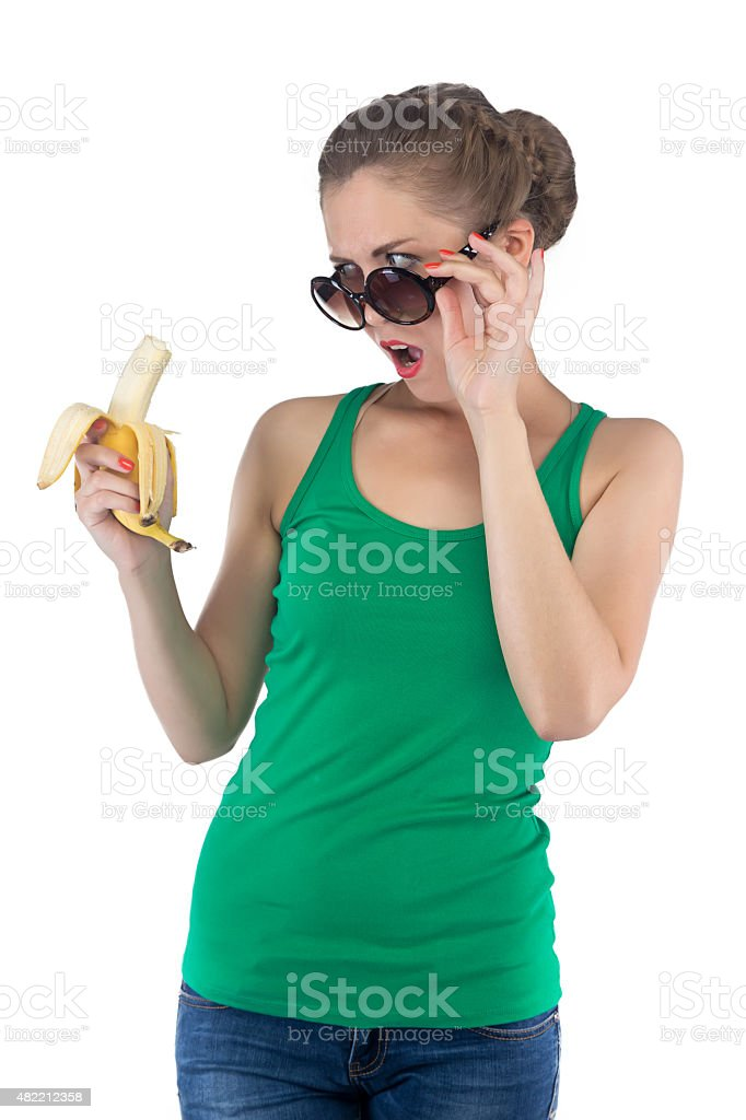Photo of surprised girl with banana and sunglasses stock photo