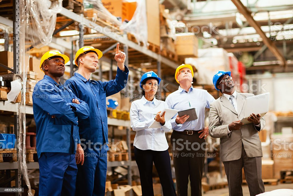 Photo of warehouse workers showing inventory stock photo