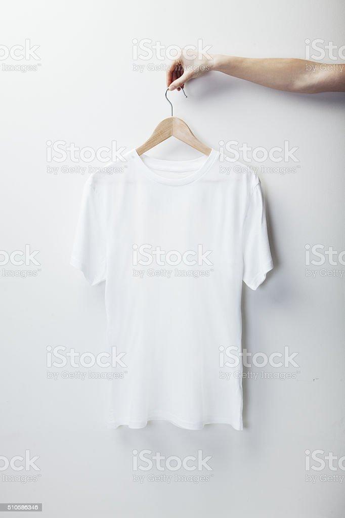 Photo of white tshirt hanging female hand stock photo
