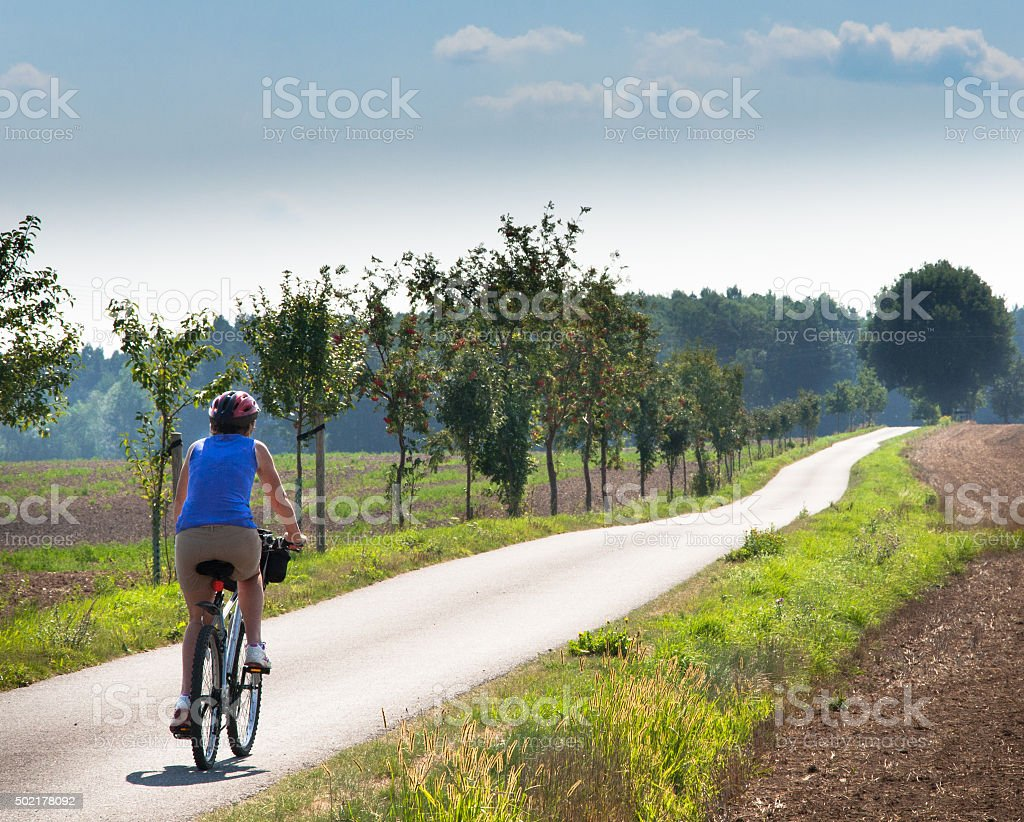 Photo of woman cycling with a long road ahead stock photo