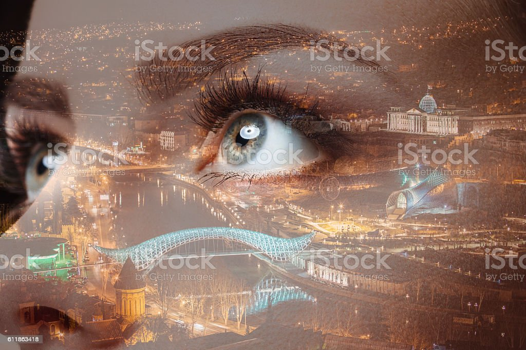 Photo of woman eye and city night lights. Double exposure stock photo