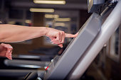Photo of Woman Running and  setting treadmill in the gym