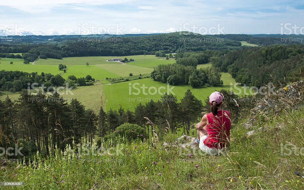 Photo of woman sitting on ridge looking at Ardenne farmland stock photo