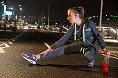 Photo of Woman Stretching Her Legs Before Workout at night
