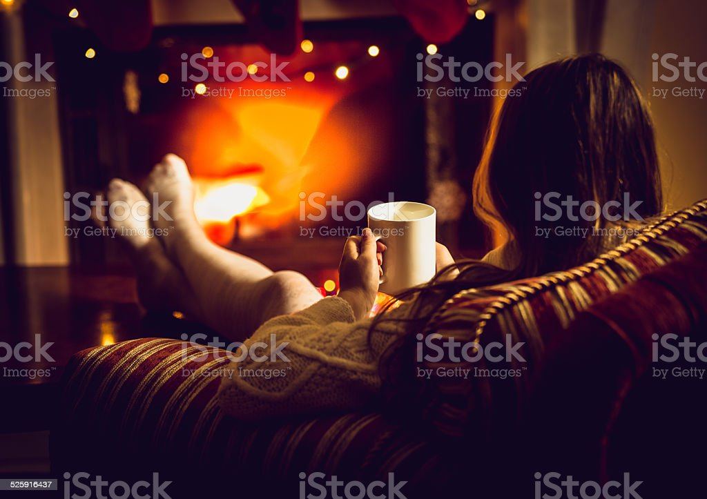 photo of woman warming up with hot tea at fireplace stock photo