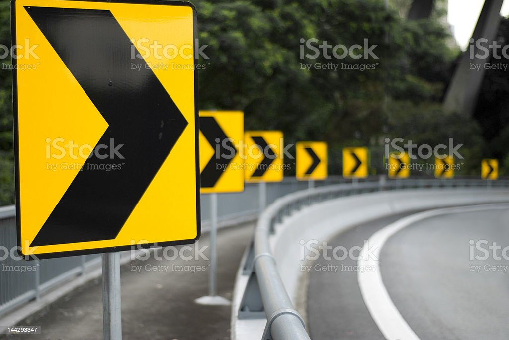 Photo of yellow signs on the road pointing to the right stock photo