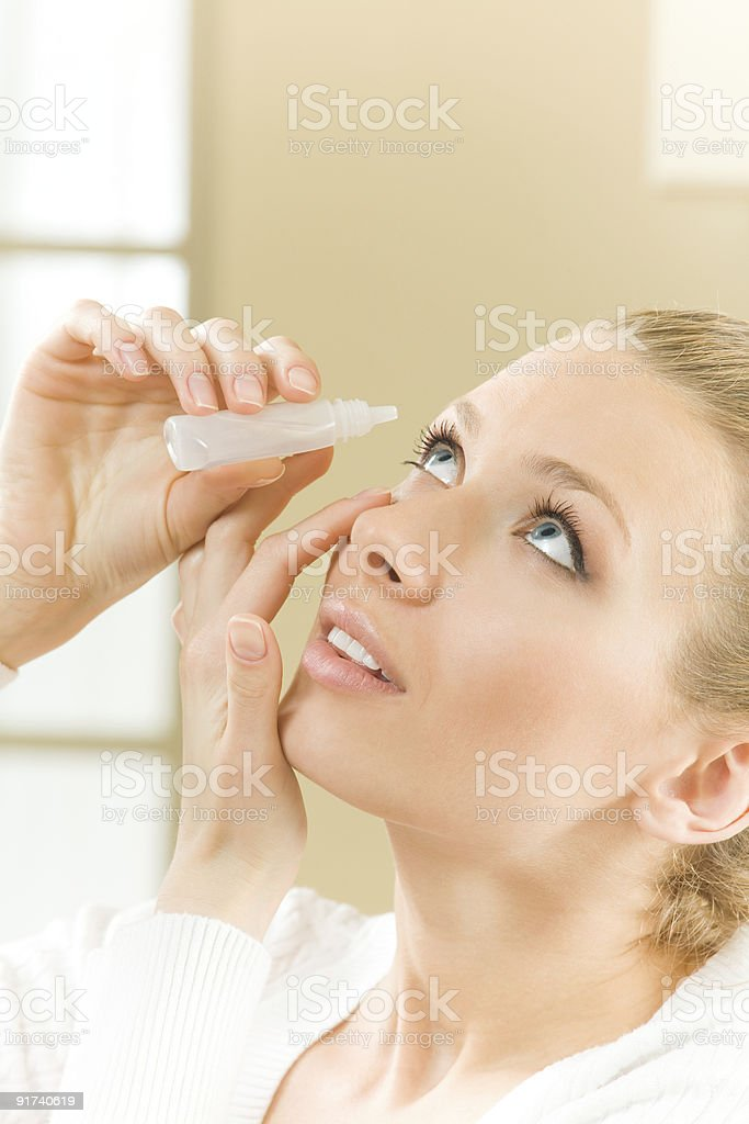Photo of young woman dripping eye with eyes drops stock photo