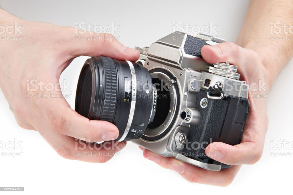 Photo SLR camera and lens in hands isolated stock photo