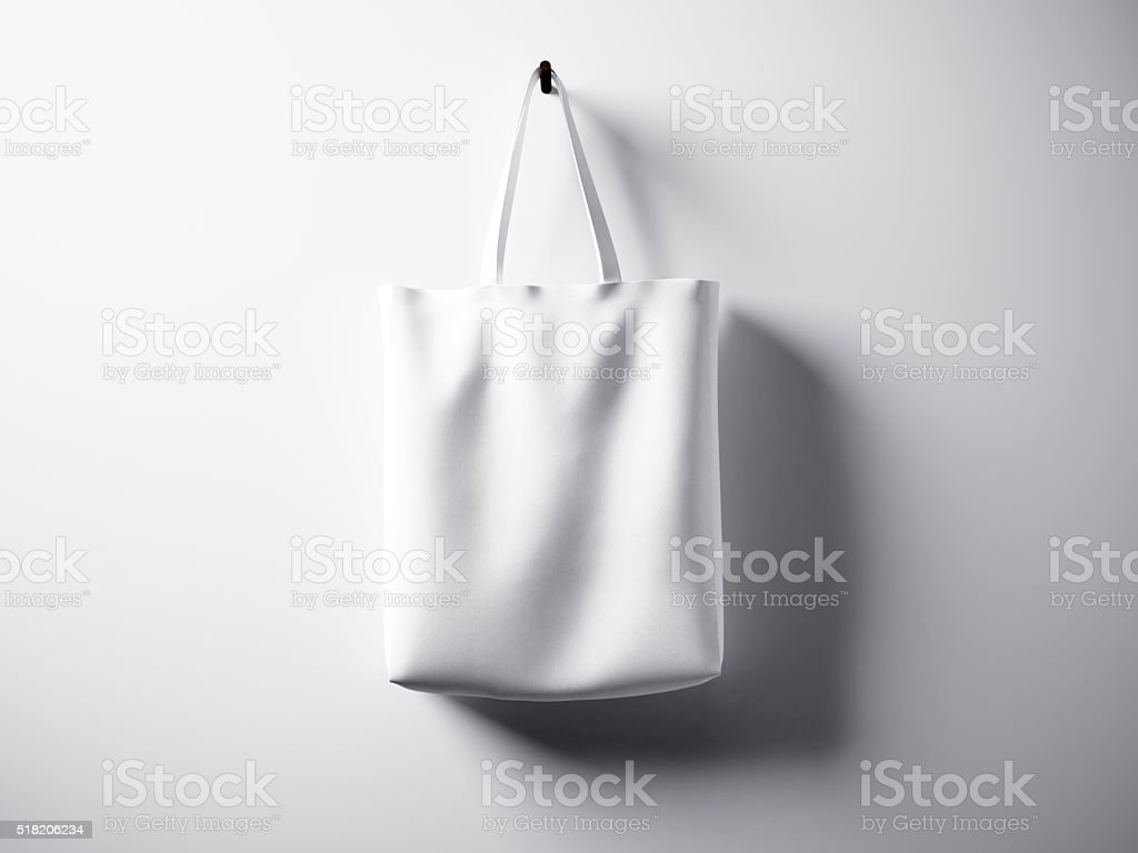 Photo white cotton textile bag hanging center. Empty abstract wall stock photo