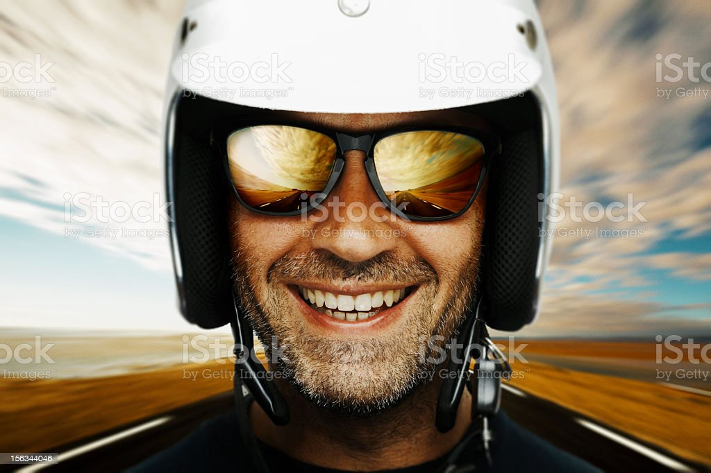Photograph of a happy male biker smiling with sky backdrop stock photo