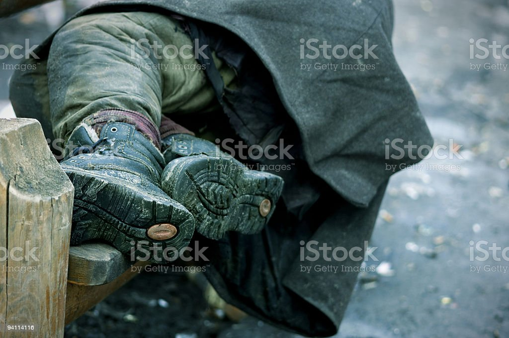 A photograph of a homeless mans legs on a bench stock photo