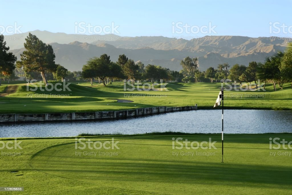 A photograph of a lush green golf course and lake royalty-free stock photo