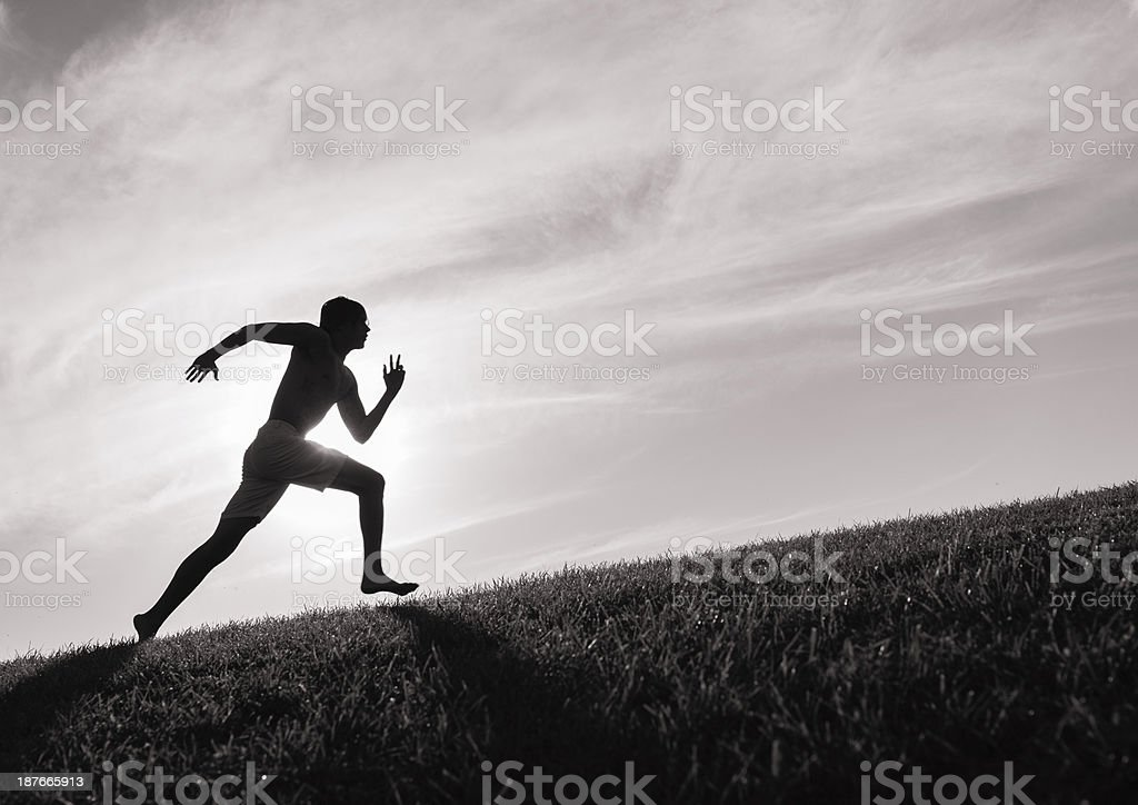 Photograph of a man in silhouette running up a hill stock photo
