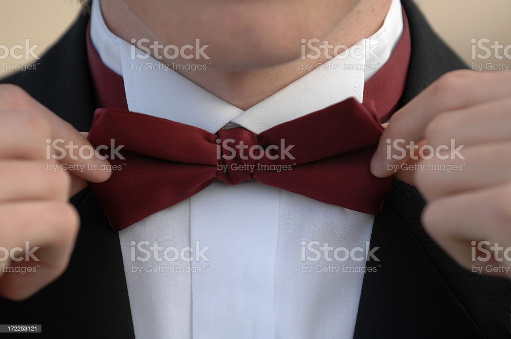 Photograph of a man tightening his red bow tie stock photo