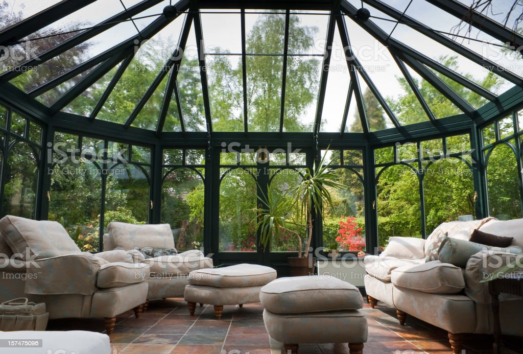 A photograph of a modern conservatory with brown furniture stock photo