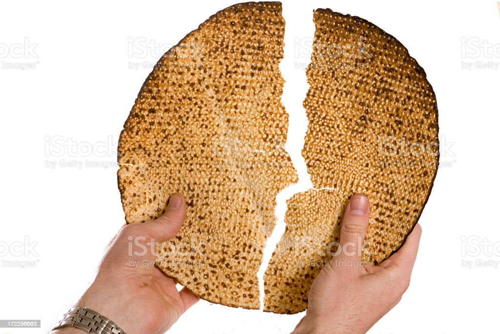 A photograph of A pair of hands breaking the Seder bread stock photo