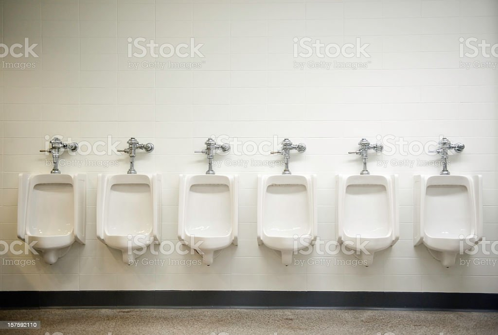 Photograph of a row of six white urinals stock photo