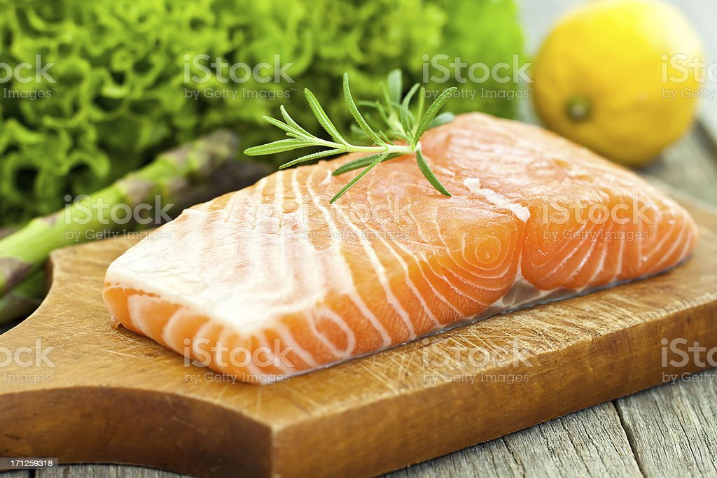 A photograph of a salmon fillet on a wooden board stock photo