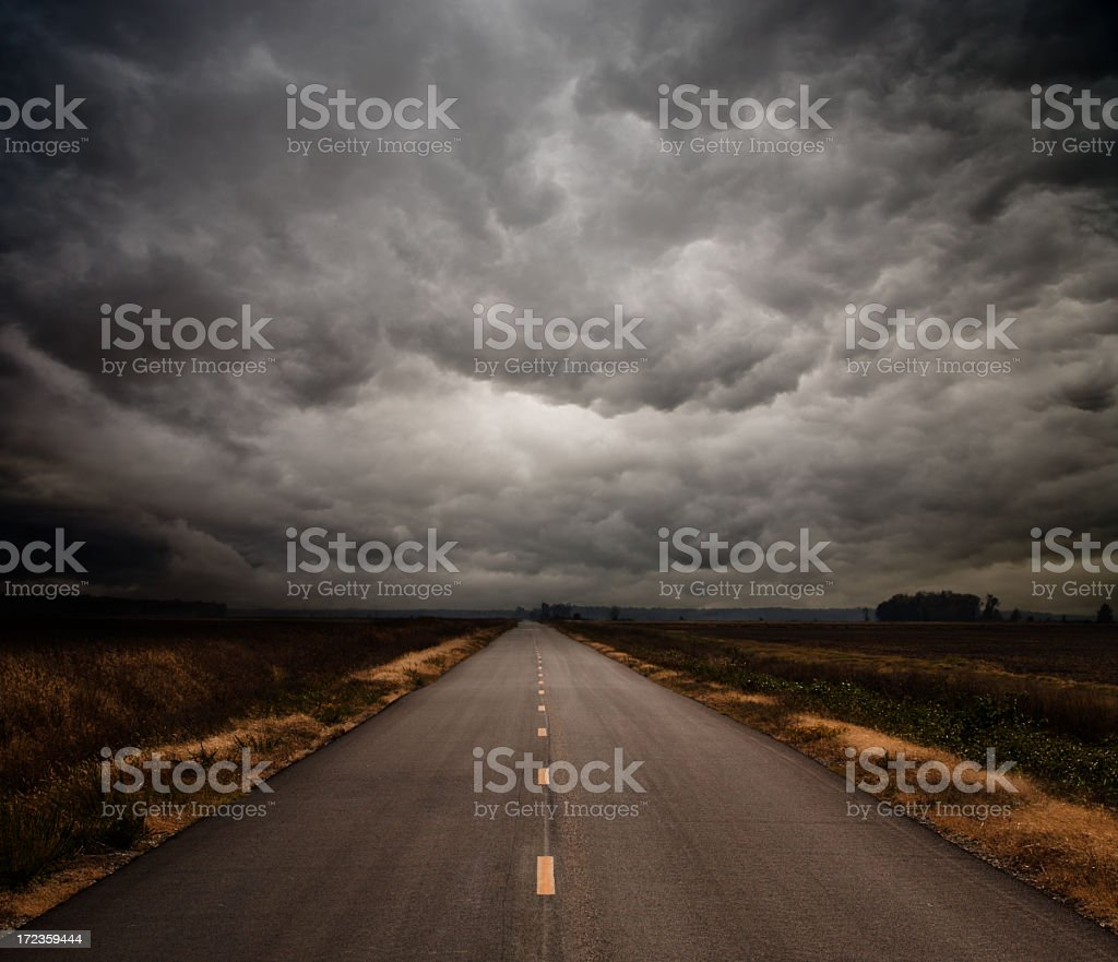 Photograph of a straight road on a cloudy day stock photo