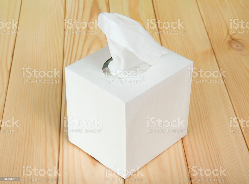 A photograph of a white tissue box on a hardwood floor stock photo