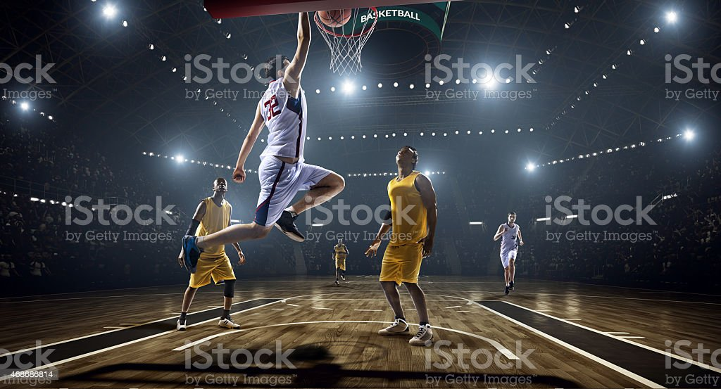 Photograph of basketball game as a slam dunk is scored stock photo