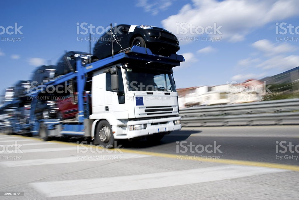Photograph of car transporter truck driving on an urban road stock photo