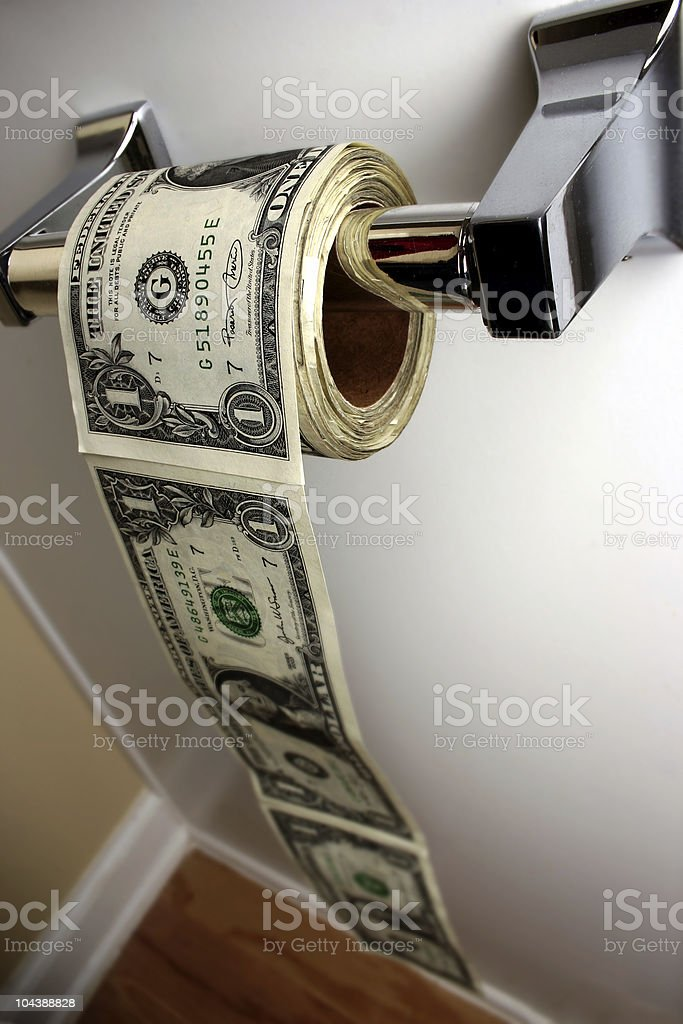 Photograph of dollar bills being used as toilet paper stock photo