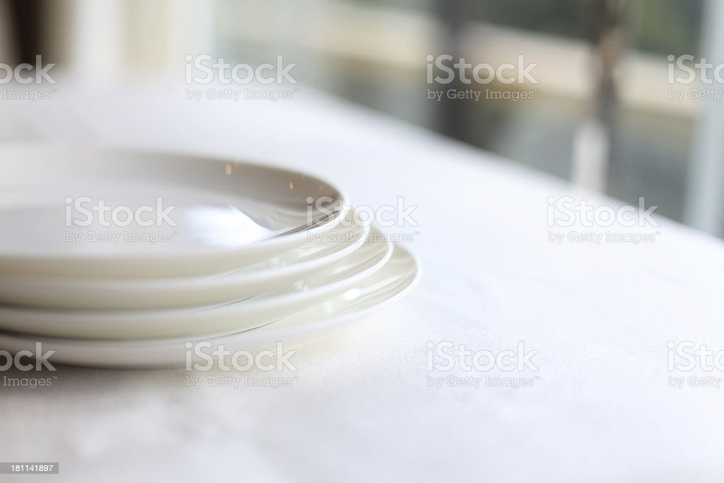 A photograph of four white plates on a stack stock photo