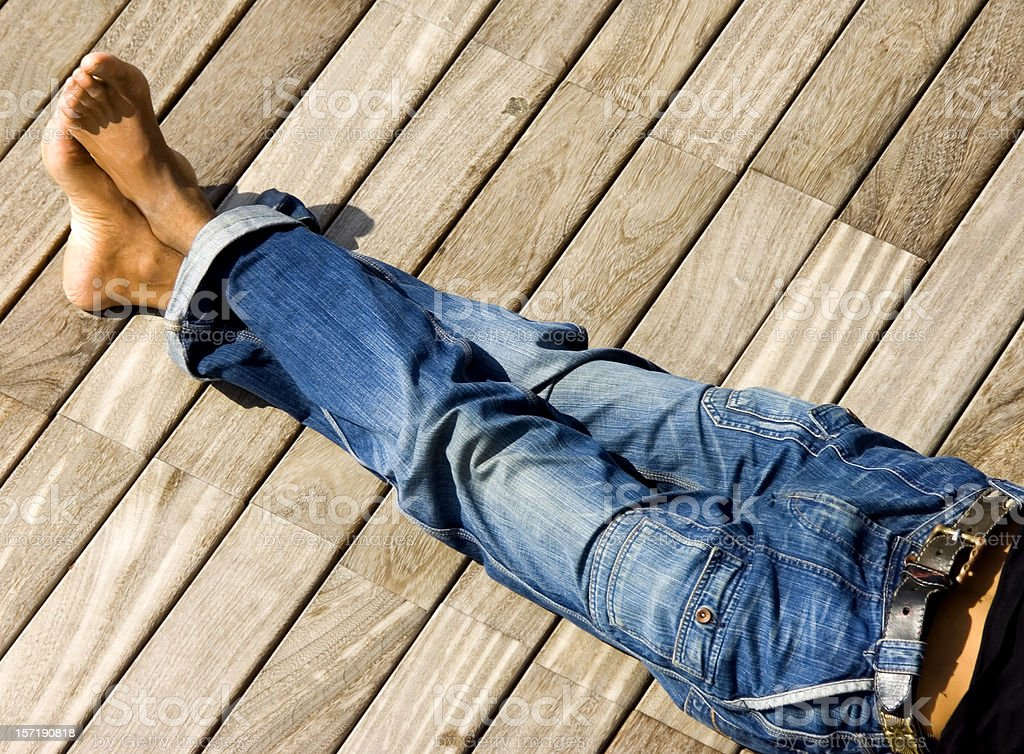 A photograph of some legs in jeans with ankles crossed royalty-free stock photo