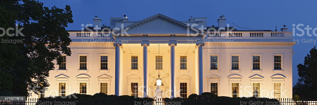 A photograph of the White House at night stock photo