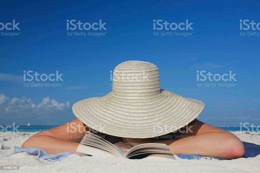 Photograph of woman lying on beach wearing sun hat reading royalty-free stock photo