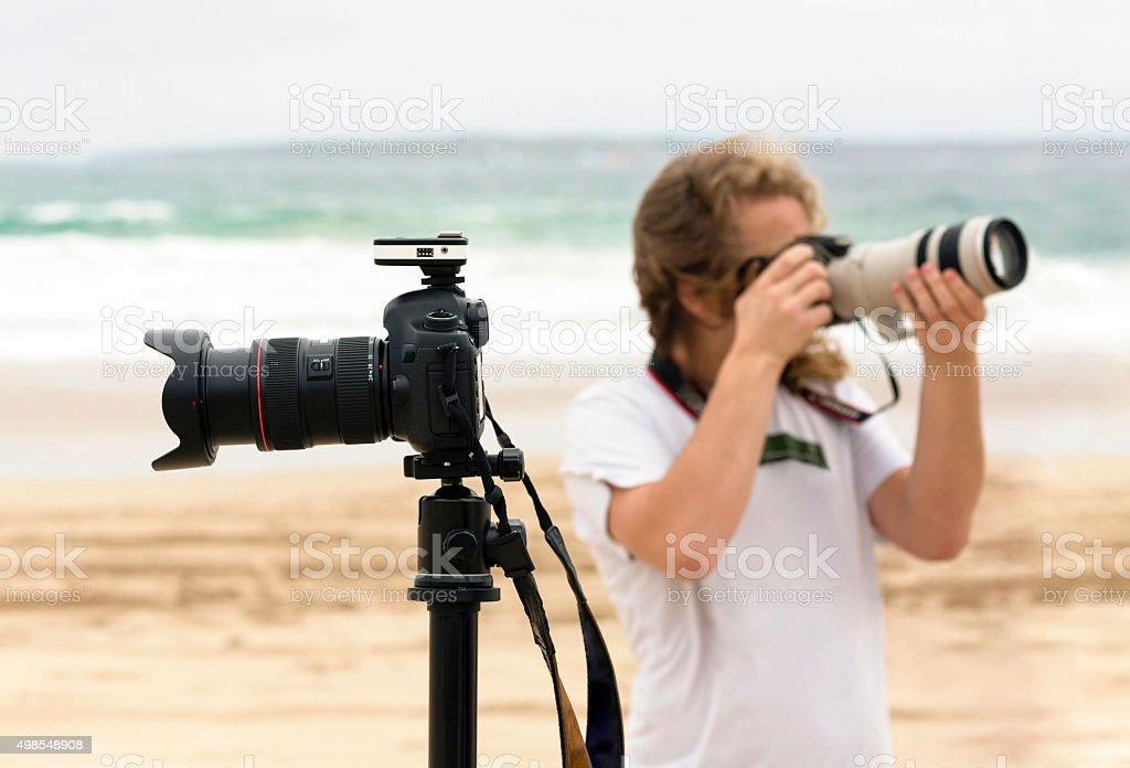 Photographer and his DSLR cameras taking shots on the beach stock photo